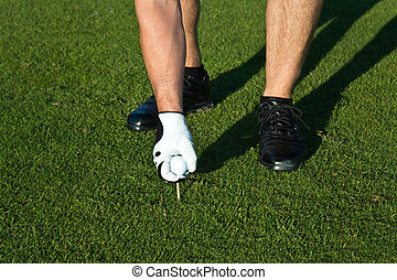 Golfer putting the ball on a tee