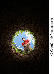 golfer putting, view from inside the hole