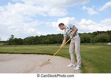 golfer racking sand - full length view of a golfer racking...