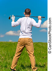 golfer resting with a golf club on his shoulders in a green field, view from the back