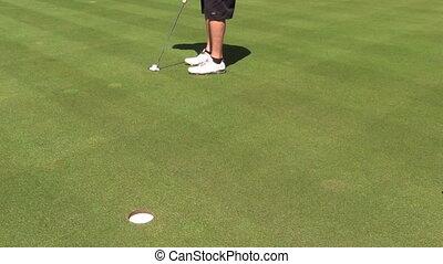 Golfer Sinking a Putt - a golfer sinks a short putt