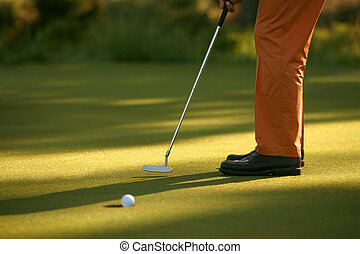 Golfer Sinking a Putt - Tight shot of a golf ball about to...
