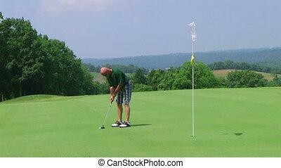Golfer Sinks Putt - Golfer sinks long putt.