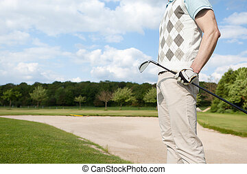 golfer standing near sand trap - mid section view of golfer...