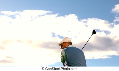 Golfer swinging his club on the course in slow motion