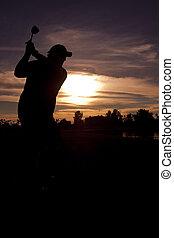Golfer Swinging in sunset