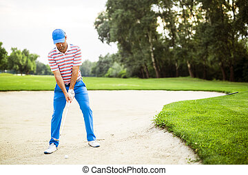 Golfer taking a bunker shot with the ball being in sand