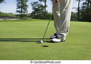 Golfer taps in with putter on green with trees near a lake -...