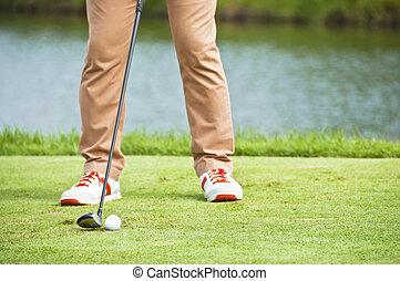Golfer tee shot address.
