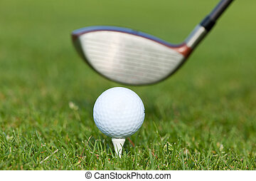 golfer teeing off - close-up of golf club with ball on tee
