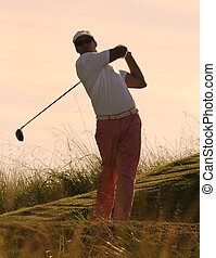 Golfer tees off at sunset