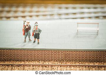 golfers - miniature train set figures on a station platform...