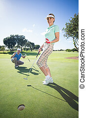 Golfing couple cheering on the putting green on a sunny day...