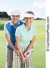 Golfing couple putting ball together smiling at camera