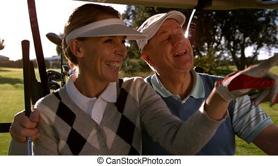 Golfing couple sitting buggy looking around the course in...