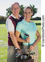 Golfing couple standing smiling at camera on a sunny day at...