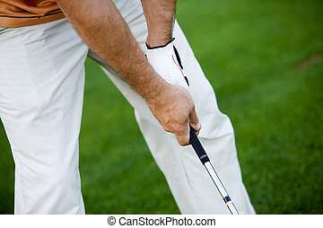 Golfing - Golfer waiting for his turn, focus on hand