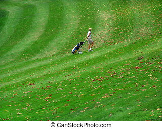 Golfing - woman on golf course walking with bag