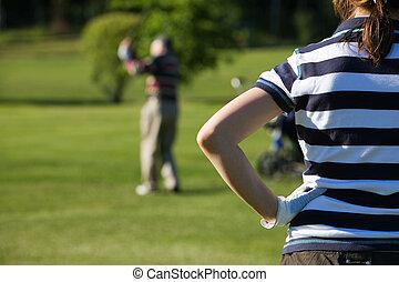 Golfing - Senior man playing golf with his grandaughter
