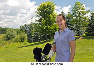Golfing woman with her golf bag on the fairway