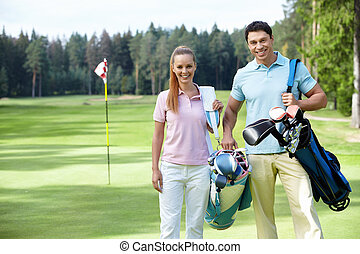Golfing - Young couple on the golf course