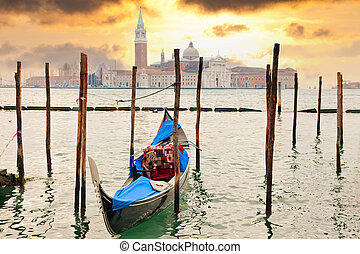 Gondola at sunset pier near in Venice, Italy
