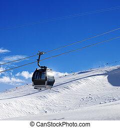 Gondola lift on ski resort at sun wind day