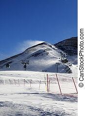 Gondola lift on ski resort at windy sun day