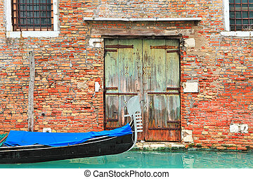 Gondola on canal and old brick house in Venice, Italy.