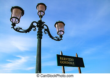 Gondola service sign and street lamp against blue sky near Piazza San Marco in Venice, Italy