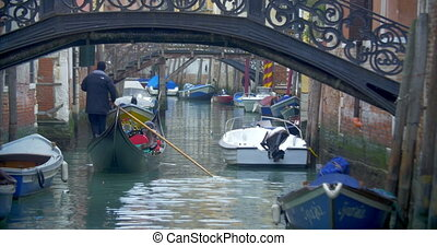Gondola with tourists sailing on Venetian canal - Tourists...