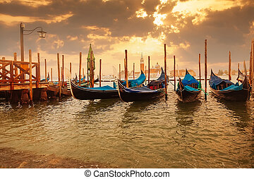 Gondolas at sunset pier near San Marco square in Venice