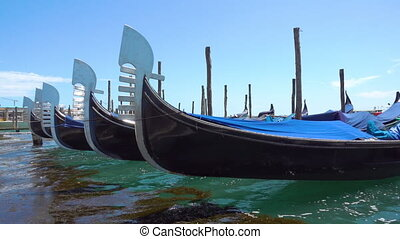 Gondolas in Venice - Snouts of moored in a row gondolas in...