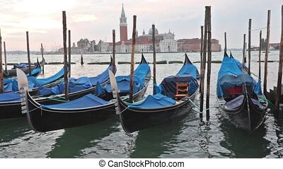 Gondolas moored by Saint Mark square in sunrise. San Giorgio...