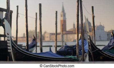 Gondolas mooring in Venice, Italy - Moored gondolas swinging...