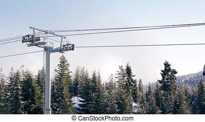 Gondolas Passing Above Snowy Trees - Gondolas with skis...