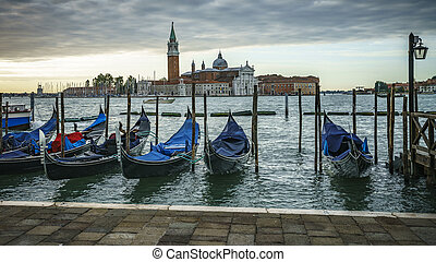 gondolas under dark cloudy sky in front of the Basilika San Giorgio Maggiore in venice