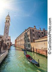Gondolier on gondola in Rio del Greci near the campanile of ...
