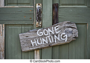 Gone Hunting. - Gone hunting sign on old door.