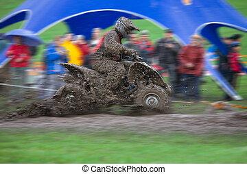 4x4 Quadrocycle ATV moving fast, lot of mud