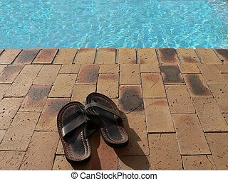 Gone Swimming - Pair of Sandals beside a Swimming Pool.
