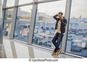 Gonna be home soon. Portrait of a handsome young man laughing speaking on the phone while waiting for his flight at the airport lounge