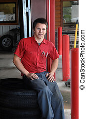 Young man rests on tire at the tire store that he works at. His uniform is red and grey and he is smiling.