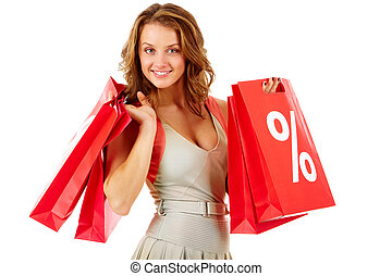 Portrait of a girl holding handbags with discount symbol, looking at camera and smiling