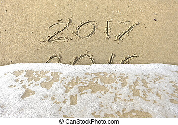 Good bye 2016 hello 2017. inscription written in the beach sand. New Year 2017 is coming concept on the sea beach