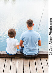 Good day for fishing. Rear view of father and son fishing ...