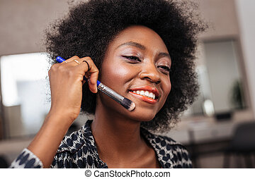 Lovely african american woman with curly hair looking happy