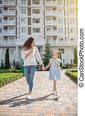 Mother and daughter walking together and eating ice-cream