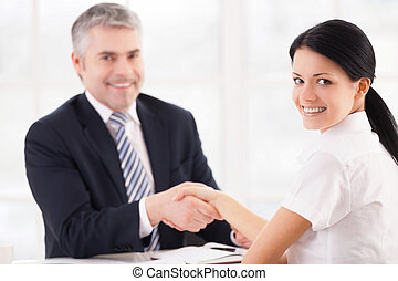 Good deal. Two people in formalwear handshaking and looking at camera while sitting at the table