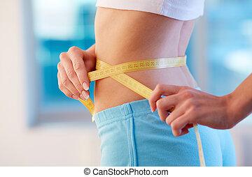 Good diet  - Close-up of slender woman measuring her waist